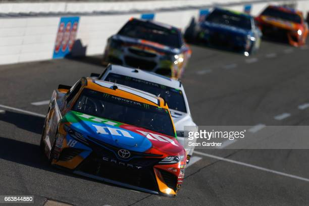 Kyle Busch driver of the MM's Toyota leads Brad Keselowski driver of the Miller Lite Ford during the Monster Energy NASCAR Cup Series STP 500 at...