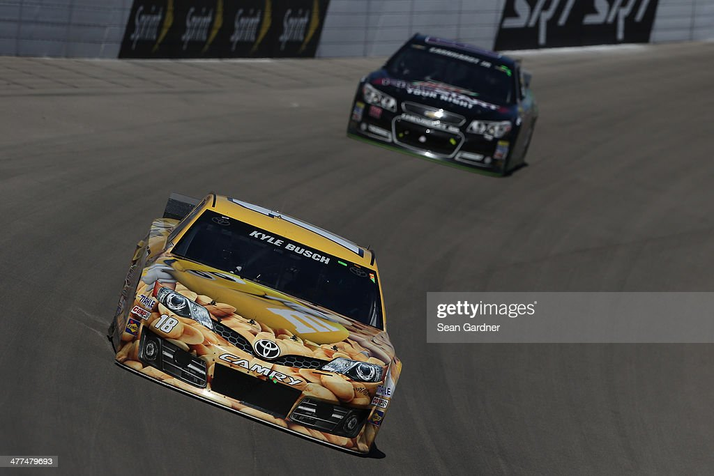 Kyle Busch, driver of the #18 M&M's Toyota, leads Dale Earnhardt Jr., driver of the #88 Mountain Dew Kickstart Chevrolet, during the NASCAR Sprint Cup Series Kobalt 400 at Las Vegas Motor Speedway on March 9, 2014 in Las Vegas, Nevada.