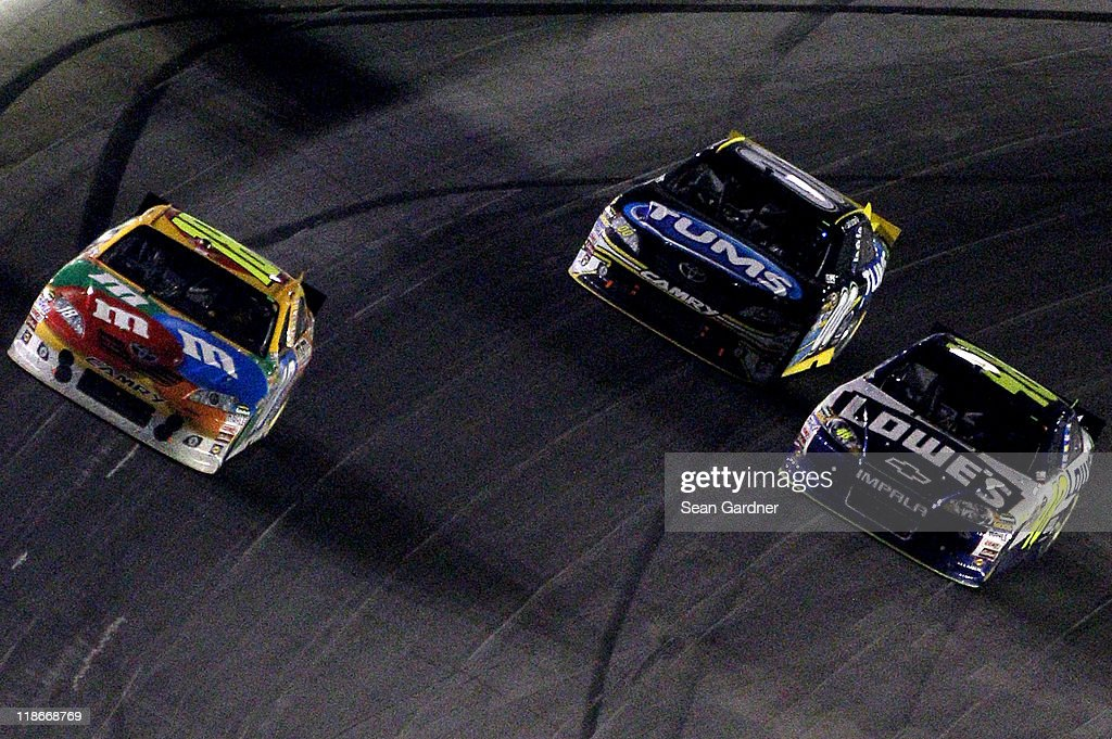 <a gi-track='captionPersonalityLinkClicked' href=/galleries/search?phrase=Kyle+Busch&family=editorial&specificpeople=211123 ng-click='$event.stopPropagation()'>Kyle Busch</a>, driver of the #18 M&M's Toyota, leads <a gi-track='captionPersonalityLinkClicked' href=/galleries/search?phrase=David+Reutimann&family=editorial&specificpeople=563987 ng-click='$event.stopPropagation()'>David Reutimann</a>, driver of the #00 Tums Toyota, and <a gi-track='captionPersonalityLinkClicked' href=/galleries/search?phrase=Jimmie+Johnson+-+Nascar+Race+Driver&family=editorial&specificpeople=171519 ng-click='$event.stopPropagation()'>Jimmie Johnson</a>, driver of the #48 Lowe's Chevrolet, during the NASCAR Sprint Cup Series Quaker State 400 at Kentucky Speedway on July 9, 2011 in Sparta, Kentucky.