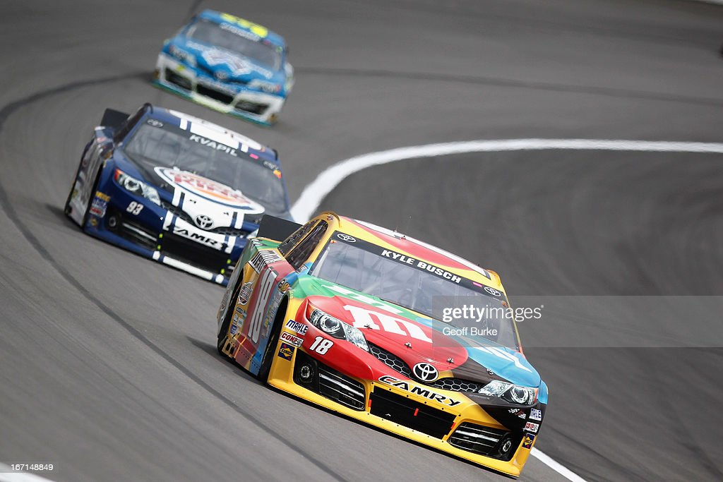 Kyle Busch, driver of the #18 M&M's Toyota, leads David Reutimann, driver of the #83 Burger King/Dr Pepper Toyota, during the NASCAR Sprint Cup Series STP 400 at Kansas Speedway on April 21, 2013 in Kansas City, Kansas.
