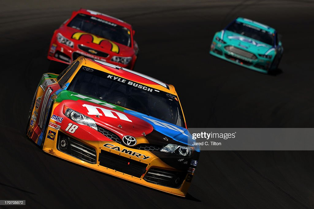 Kyle Busch, driver of the #18 M&M's Toyota, leads Jamie McMurray, driver of the #1 McDonald's Chevrolet, and Ricky Stenhouse Jr., driver of the #17 Zest Ford, during the NASCAR Sprint Cup Series Quicken Loans 400 at Michigan International Speedway on June 16, 2013 in Brooklyn, Michigan.