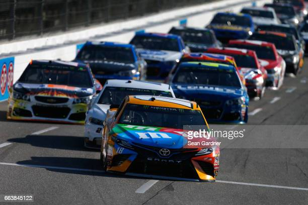 Kyle Busch driver of the MM's Toyota leads the field during a restart during the Monster Energy NASCAR Cup Series STP 500 at Martinsville Speedway on...