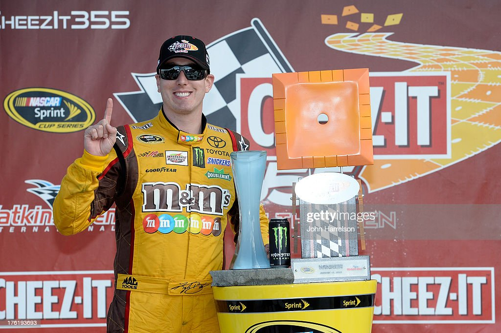 Kyle Busch, driver of the #18 M&M's Toyota, poses for a photo after winning the NASCAR Sprint Cup Series Cheez-It 355 at The Glen at Watkins Glen International on August 11, 2013 in Watkins Glen, New York.