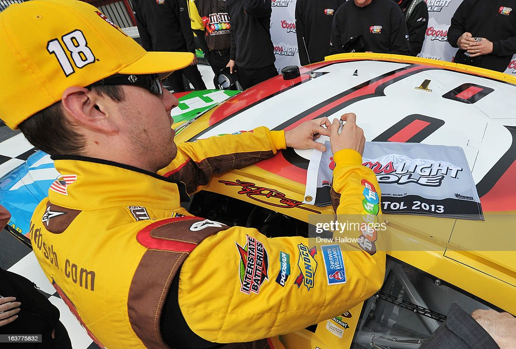 Kyle Busch, driver of the #18 M&M's Toyota, signs the pole award in Victory Lane after qualifying for the pole position in the NASCAR Sprint Cup Series Food City 500 at Bristol Motor Speedway on March 15, 2013 in Bristol, Tennessee.
