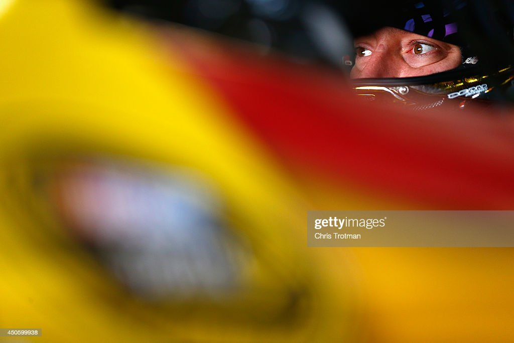 Kyle Busch, driver of the #18 M&M's Toyota, sits in his car in the garage area during practice for the NASCAR Sprint Cup Series Quicken Loans 400 at Michigan International Speedway on June 14, 2014 in Brooklyn, Michigan.
