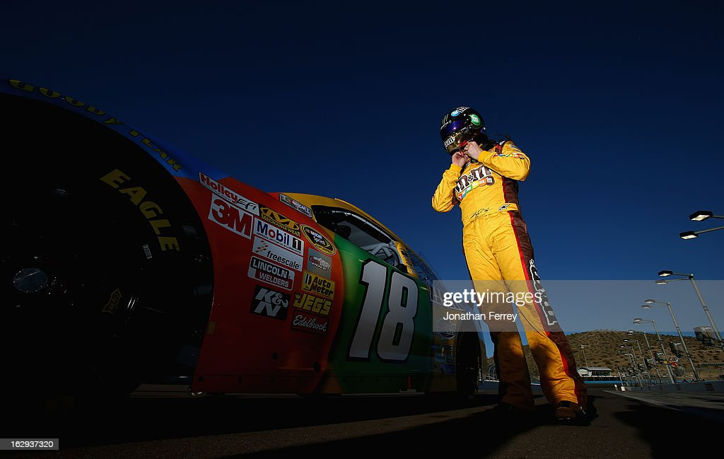 Kyle Busch, driver of the #18 M&M's Toyota, stands by his car on the grid during qualifying for the NASCAR Sprint Cup Series Subway Fresh Fit 500 at Phoenix International Raceway on March 1, 2013 in Avondale, Arizona.