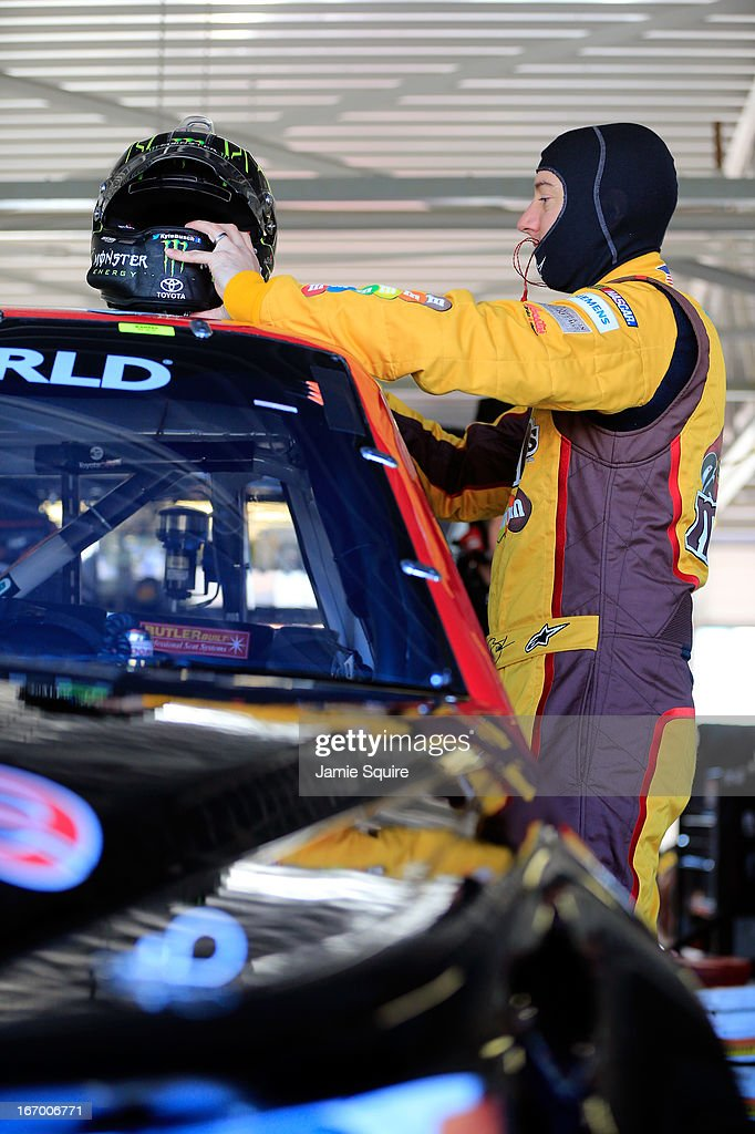 Kyle Busch, driver of the #18 M&M's Toyota, stands in the garage area during practice for the NASCAR Sprint Cup Series STP 400 at Kansas Speedway on April 19, 2013 in Kansas City, Kansas.