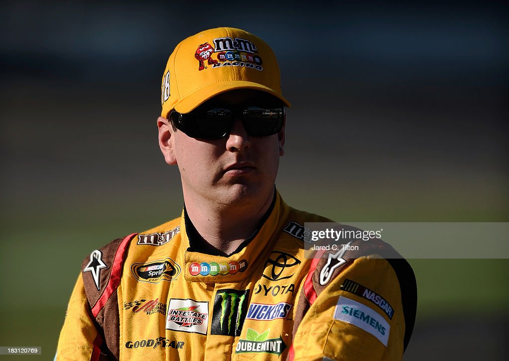 <a gi-track='captionPersonalityLinkClicked' href=/galleries/search?phrase=Kyle+Busch&family=editorial&specificpeople=211123 ng-click='$event.stopPropagation()'>Kyle Busch</a>, driver of the #18 M&M's Toyota, stands on the grid during qualifying for the NASCAR Sprint Cup Series 13th Annual Hollywood Casino 400 at Kansas Speedway on October 4, 2013 in Kansas City, Kansas.