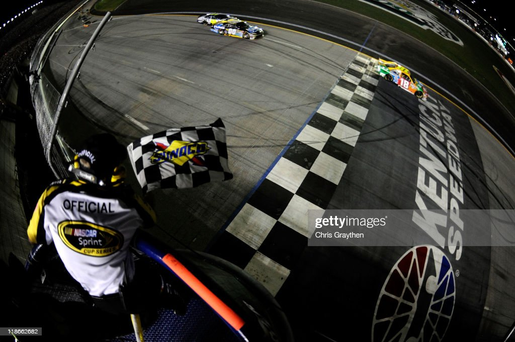 <a gi-track='captionPersonalityLinkClicked' href=/galleries/search?phrase=Kyle+Busch&family=editorial&specificpeople=211123 ng-click='$event.stopPropagation()'>Kyle Busch</a>, driver of the #18 M&M's Toyota, takes the checkered flag as he crosses the finish line to win the NASCAR Sprint Cup Series Quaker State 400 at Kentucky Speedway on July 9, 2011 in Sparta, Kentucky.