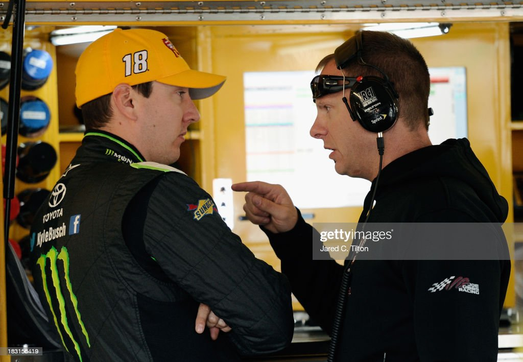 Kyle Busch (L), driver of the #18 M&M's Toyota, talks with crew chief Dave Rogers in the garage area after an on track incident during practice for the NASCAR Sprint Cup Series 13th Annual Hollywood Casino 400 at Kansas Speedway on October 5, 2013 in Kansas City, Kansas. Busch wore his Nationwide firesuit during Cup practice.