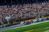 Kyle Busch driver of the Monster Energy Toyota and Brad Keselowski driver of the Discount Tire Ford lead the field past the green flag to start the...