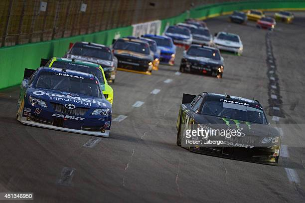 Kyle Busch driver of the Monster Energy Toyota and Elliott Sadler driver of the OneMain Financial Toyota race ahead of a pack of cars during the...