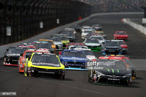 Kyle Busch driver of the Monster Energy Toyota and Paul Menard driver of the Richmond/Menards Chevrolet lead a pack of cars into turn one during the...