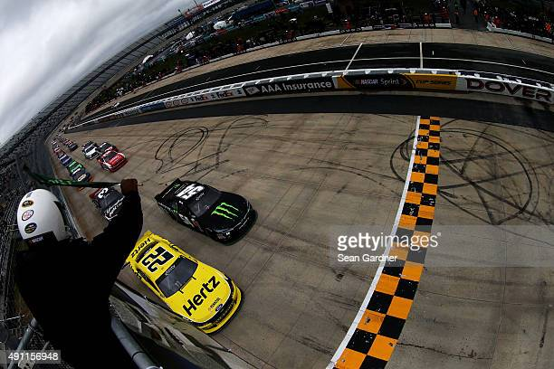 Kyle Busch driver of the Monster Energy Toyota and Ryan Blaney driver of the Hertz Ford lead the field to the green flag for the running of the...