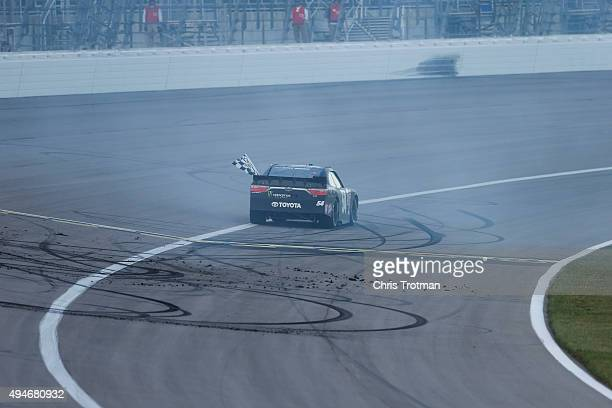 Kyle Busch driver of the Monster Energy Toyota celebrates with a burnout after winning during the NASCAR XFINITY Series Kansas Lottery 300 at Kansas...