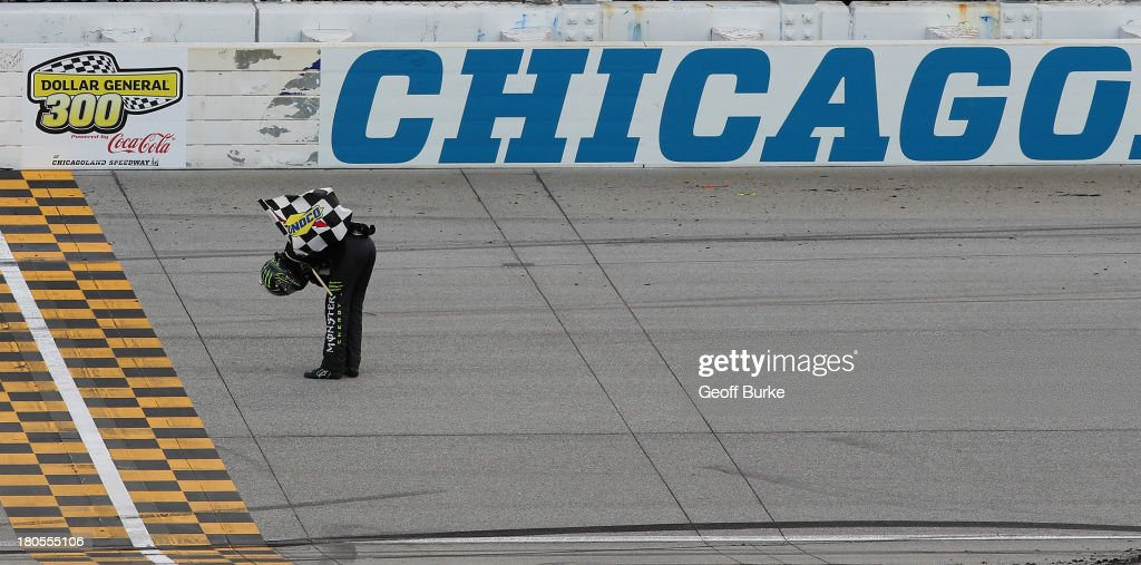 Kyle Busch, driver of the #54 Monster Energy Toyota, celebrates with the checkered flag after winning the NASCAR Nationwide Series Dollar General 300 Powered by Coca-Cola at Chicagoland Speedway on September 14, 2013 in Joliet, Illinois.