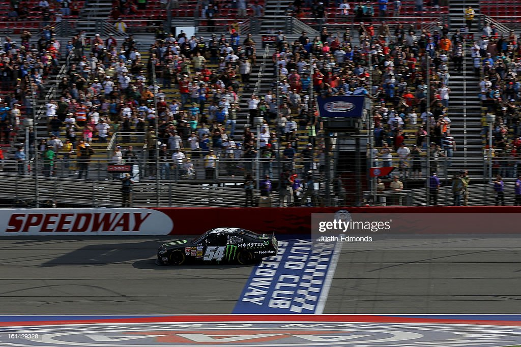 Kyle Busch, driver of the #54 Monster Energy Toyota, crosses the finish line to win the NASCAR Nationwide Series Royal Purple 300 at Auto Club Speedway on March 23, 2013 in Fontana, California.