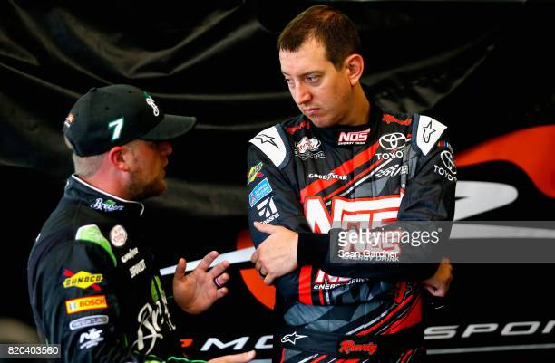 Kyle Busch driver of the NOS Energy Drink Rowdy Toyota talks with Justin Allgaier driver of the Breyers Chevrolet during practice for the NASCAR...