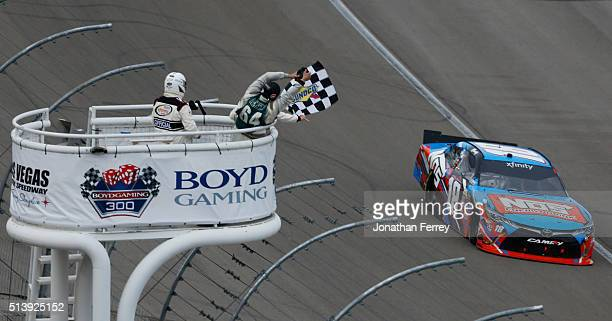 Kyle Busch driver of the NOS Energy Drink Toyota crosses the finish line to win the NASCAR Xfinity Series Boyd Gaming 300 at Las Vegas Motor Speedway...