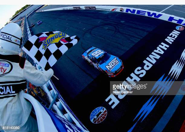 Kyle Busch driver of the NOS Energy Drink Toyota crosses the finish line to win the NASCAR XFINITY Series Overton's 200 at New Hampshire Motor...