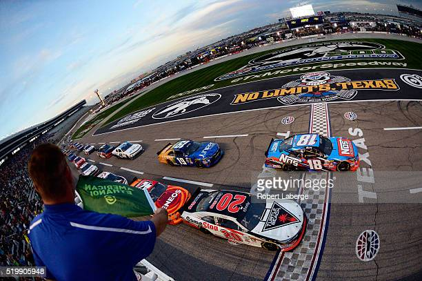 Kyle Busch driver of the NOS Energy Drink Toyota leads the field past the green flag to start the NASCAR XFINITY Series O'Reilly Auto Parts 300 at...