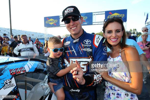 Kyle Busch driver of the NOS Energy Drink Toyota poses with his wife Samantha and their son Brexton in Victory Lane after winning the NASCAR XFINITY...