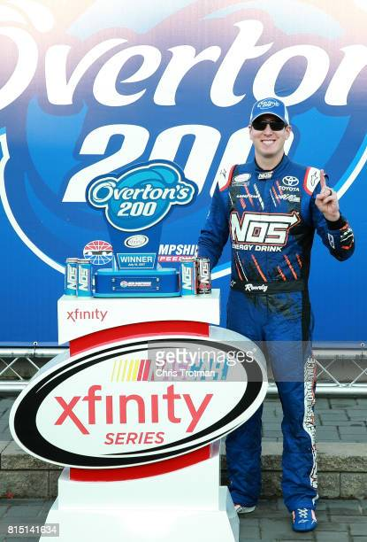 Kyle Busch driver of the NOS Energy Drink Toyota poses with the trophy in Victory Lane after winning the NASCAR XFINITY Series Overton's 200 at New...