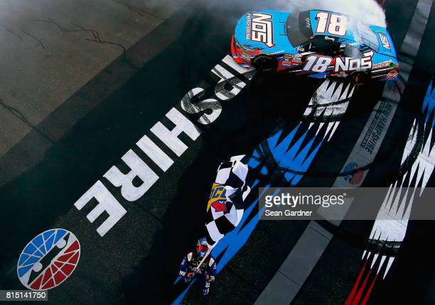 Kyle Busch driver of the NOS Energy Drink Toyota receives the checkered flag after winning the NASCAR XFINITY Series Overton's 200 at New Hampshire...