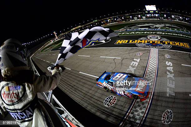Kyle Busch driver of the NOS Energy Drink Toyota takes the checkered flag to win the NASCAR XFINITY Series O'Reilly Auto Parts 300 at Texas Motor...