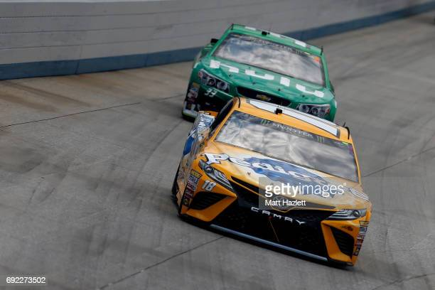 Kyle Busch driver of the Pedigree Petcare Toyota leads Jeffrey Earnhardt driver of the Hulu Chevrolet during the Monster Energy NASCAR Cup Series AAA...