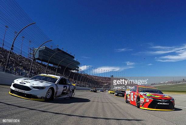 Kyle Busch driver of the Skittles Toyota and Brad Keselowski driver of the Miller Lite Ford lead the field during the pace laps prior to the NASCAR...