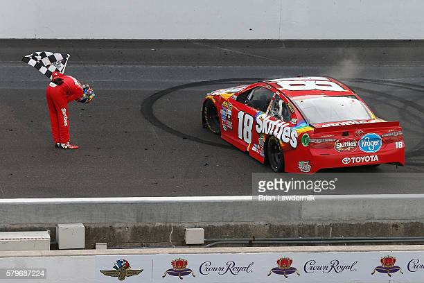 Kyle Busch driver of the Skittles Toyota celebrates after winning the NASCAR Sprint Cup Series Crown Royal Presents the Combat Wounded Coalition 400...