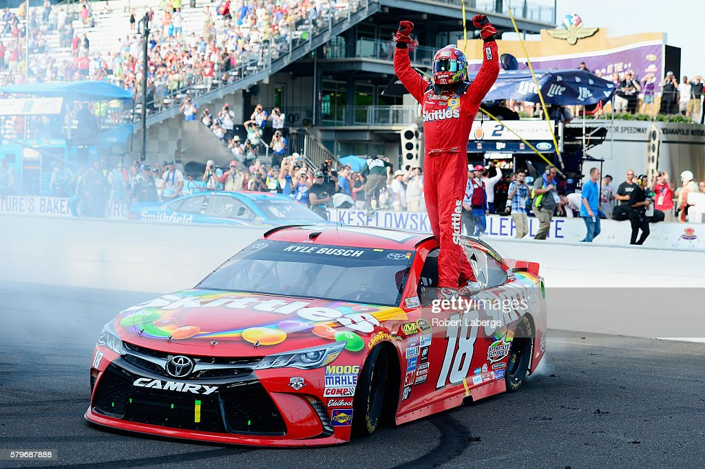 Kyle Busch, driver of the #18 Skittles Toyota, celebrates winning the NASCAR Sprint Cup Series Crown Royal Presents the Combat Wounded Coalition 400 at Indianapolis Motor Speedway on July 24, 2016 in Indianapolis, Indiana.
