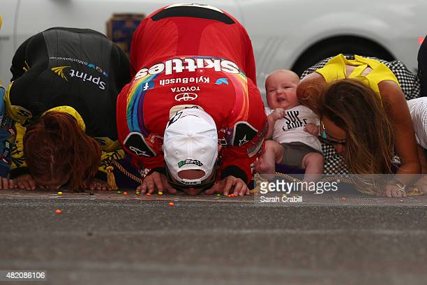Kyle Busch driver of the Skittles Toyota celebrates with his wife Samantha and their son Brexton by kissing the bricks after winning the NASCAR...
