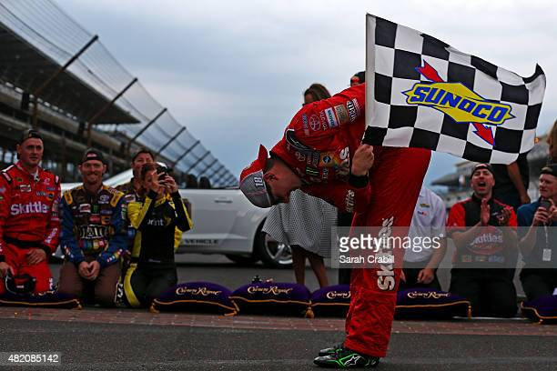 Kyle Busch driver of the Skittles Toyota celebrates with the checkered flag after winning the NASCAR Sprint Cup Series Crown Royal Presents the Jeff...
