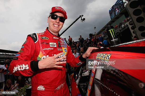Kyle Busch driver of the Skittles Toyota places the winner's decal in Victory Lane after winning the NASCAR Sprint Cup Series Crown Royal Presents...