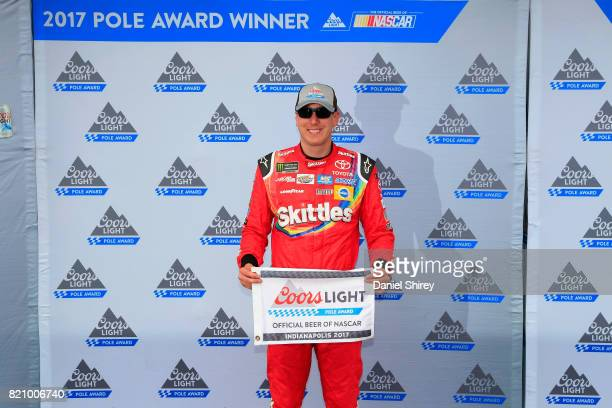 Kyle Busch driver of the Skittles Toyota poses with the Coors Light Pole Award after qualifying for pole position for the Monster Energy NASCAR Cup...