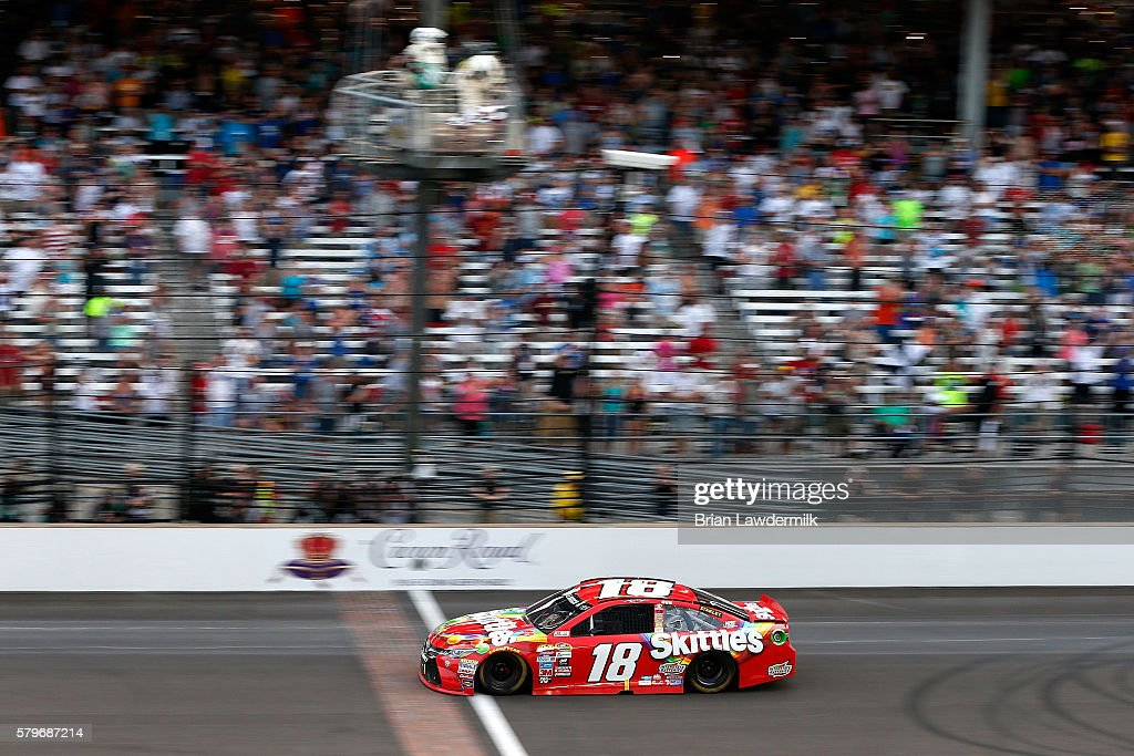 Kyle Busch, driver of the #18 Skittles Toyota, takes the checkered flag to win the NASCAR Sprint Cup Series Crown Royal Presents the Combat Wounded Coalition 400 at Indianapolis Motor Speedway on July 24, 2016 in Indianapolis, Indiana.