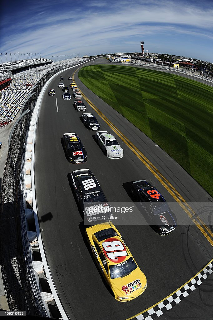 Kyle Busch, driver of the #18 Toyota, and Aric Almirola, driver of the #43 Ford, lead a group of cars across the start/finish line during NASCAR Sprint Cup Series Preseason Thunder testing at Daytona International Speedway on January 11, 2013 in Daytona Beach, Florida.