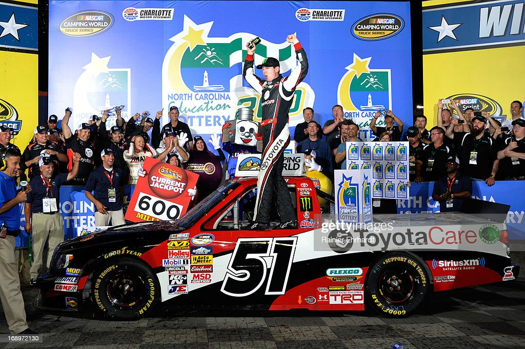 Kyle Busch driver of the Toyota Care Toyota celebrates in Victory Lane after winning the NASCAR Camping World Truck Series North Carolina Education...
