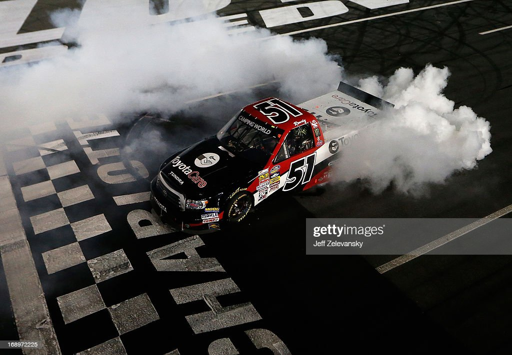 <a gi-track='captionPersonalityLinkClicked' href=/galleries/search?phrase=Kyle+Busch&family=editorial&specificpeople=211123 ng-click='$event.stopPropagation()'>Kyle Busch</a>, driver of the #51 Toyota Care Toyota, celebrates with a burnout after winning the NASCAR Camping World Truck Series North Carolina Education Lottery 200 at Charlotte Motor Speedway on May 17, 2013 in Concord, North Carolina.
