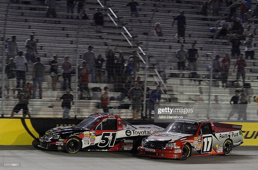 Kyle Busch, driver of the #51 ToyotaCare Toyota, races Timothy Peters, driver of the #17 Parts Plus Toyota, to the finish line during the UNOH 200 at Bristol Motor Speedway on August 21, 2013 in Bristol, Tennessee.
