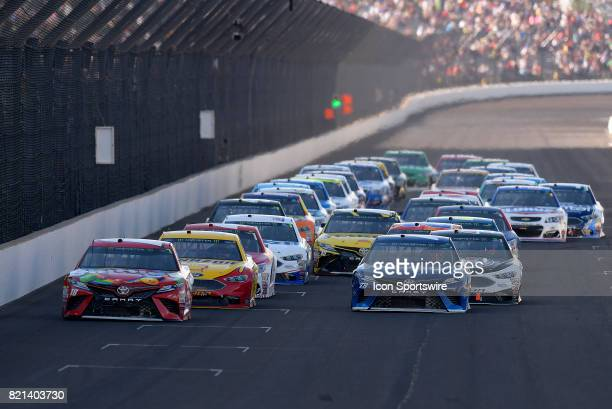 Kyle Busch Joe Gibbs Racing Toyota Camry and Martin Truex Jr Furniture Row Racing Toyota Camry lead the field to a restart during the NASCAR Monster...