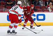 Kyle Chipchura of the Arizona Coyotes passes the puck around Alexander Semin of the Carolina Hurricanes during the NHL game at Gila River Arena on...