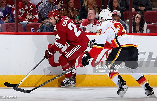 Kyle Chipchura of the Arizona Coyotes skates with the puck ahead of Drew Shore of the Calgary Flames during the first period of the NHL game at Gila...