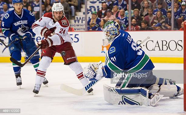 Kyle Chipchura of the Arizona Coyotes tries to get his stick on the airborne puck after goalie Eddie Lack of the Vancouver Canucks made the initial...