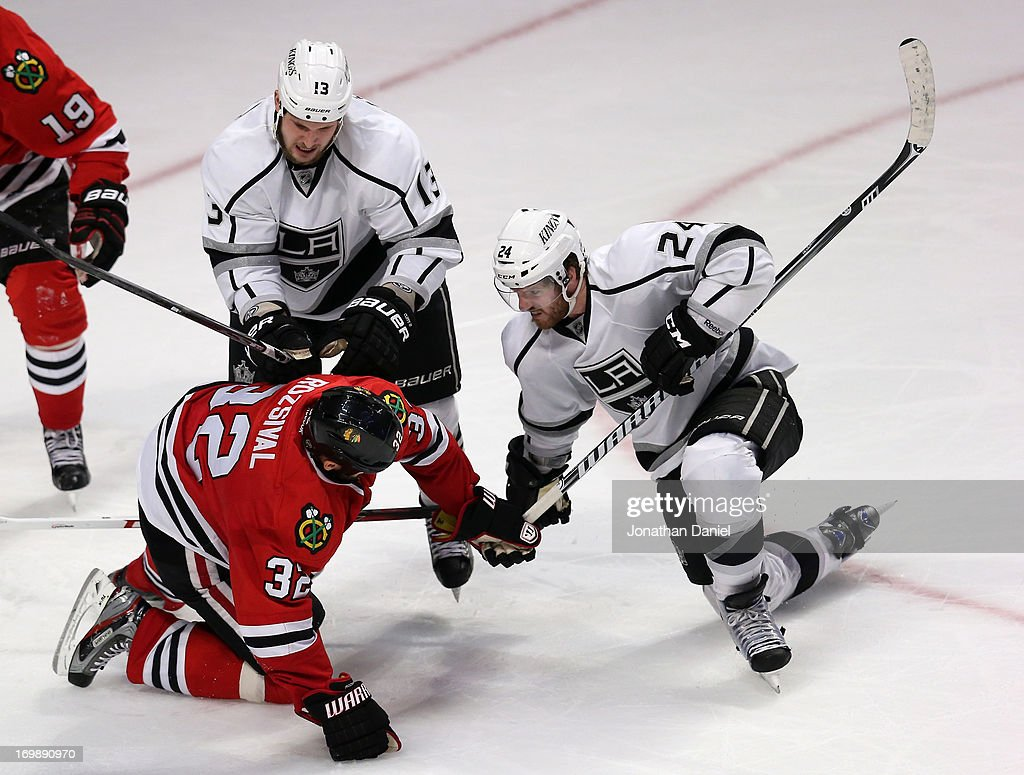 Kyle Clifford and Colin Fraser of the Los Angeles Kings rough up Michal Rozsival of the Chicago Blackhawks after Rozsival cross checked Fraser down...