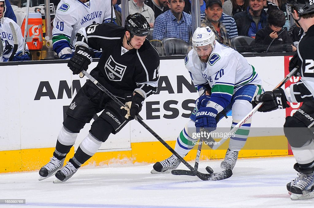 Kyle Clifford #13 of the Los Angeles Kings battles for the puck against Chris Higgins #20 of the Vancouver Canucks at Staples Center on March 23, 2013 in Los Angeles, California.