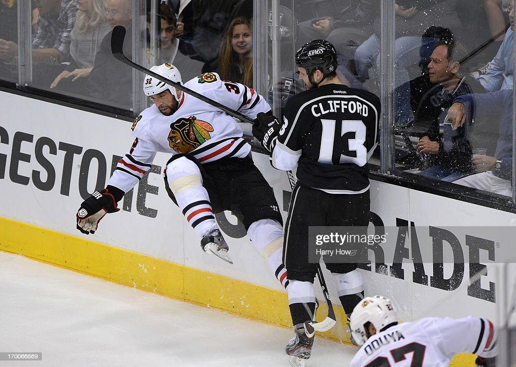 <a gi-track='captionPersonalityLinkClicked' href=/galleries/search?phrase=Kyle+Clifford&family=editorial&specificpeople=4640225 ng-click='$event.stopPropagation()'>Kyle Clifford</a> #13 of the Los Angeles Kings checks <a gi-track='captionPersonalityLinkClicked' href=/galleries/search?phrase=Michal+Rozsival&family=editorial&specificpeople=216462 ng-click='$event.stopPropagation()'>Michal Rozsival</a> #32 of the Chicago Blackhawks at the end boards in the second period of Game Four of the Western Conference Final during the 2013 NHL Stanley Cup Playoffs at Staples Center on June 6, 2013 in Los Angeles, California.