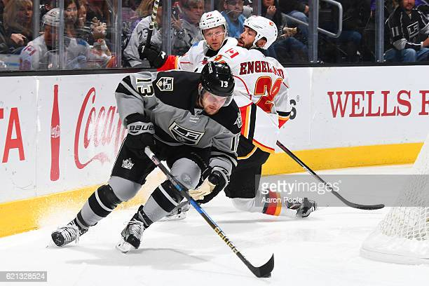 Kyle Clifford of the Los Angeles Kings gains control of the puck against Brett Kulak and Deryk Engelland of the Calgary Flames on November 5 2016 at...